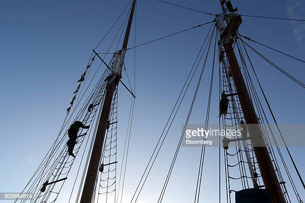 An employee places bunting on to the rigging of a boat outside at the 2016 London Boat Show on display at the ExCel exhibition centre in London UK on...