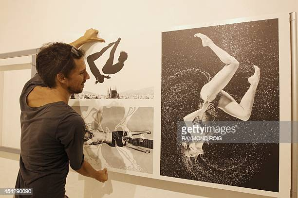 An employee places framed photos by Australian photographer and 2014 World Press Photo Contest winner in the sports action stories category Quinn...