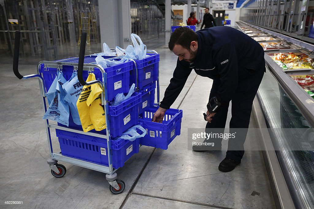 An employee places frozen food orders into crates at a Tesco Plc on-line distribution center, in Erith, U.K., on Wednesday, Nov. 27, 2013. Tesco Plc, the U.K.'s largest retailer, will sell land near some of its Polish hypermarkets to attract additional services around those stores. Photographer: Simon Dawson/Bloomberg via Getty Images