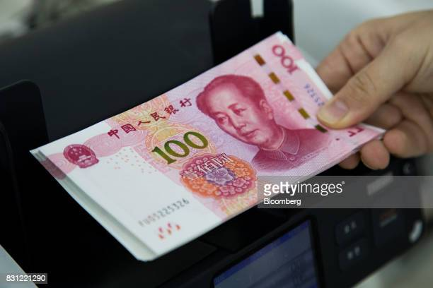 An employee places genuine Chinese onehundred yuan banknotes into a counting machine at the Counterfeit Notes Response Center of KEB Hana Bank in...