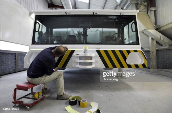 An employee places hazard stickers to the front of an aviation towing tractor at the Douglas Equipment plant owned by CurtissWright Corp in...