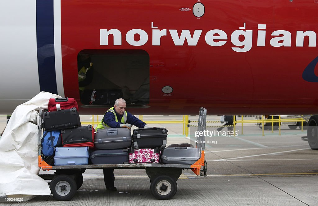 An employee places luggage from a Boeing 737-800 aircraft, operated by Norwegian Air Shuttle AS, onto a trolley at Gatwick airport in Crawley, U.K., on Thursday, Jan. 10, 2013. Gatwick, acquired by Global Infrastructure Partners Ltd. in 2009 after regulators sought a breakup of BAA Ltd., owner of the larger Heathrow hub, is 30 miles (48 kilometers) south of London and serves about 200 destinations, more than any other U.K. airport, according to flight schedule data provider OAG. Photographer: Chris Ratcliffe/Bloomberg via Getty Images