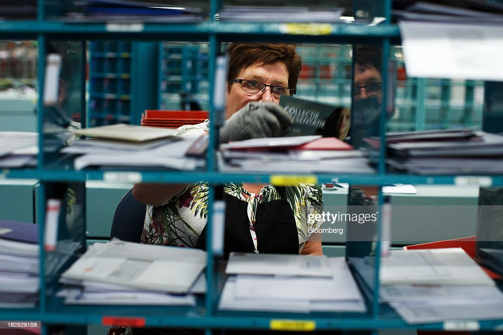An employee places mail into pigeon-holes at the PostNL NV sorting center in Nieuwegein, Netherlands, on Friday, Sept. 27, 2013. PostNL NV rose the most in two months on Sept. 19 after the Dutch postal operator raised its full-year forecast and announced higher prices for stamps. Photographer: Jasper Juinen/Bloomberg via Getty Images