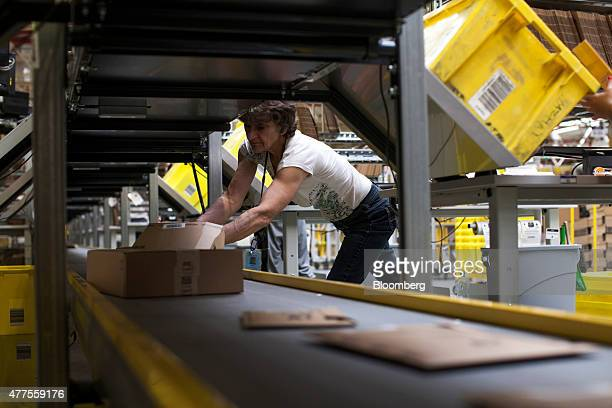 An employee places packaged goods onto a conveyor belt as she processes customer orders at the Amazoncom Inc fulfillment center in Poznan Poland on...