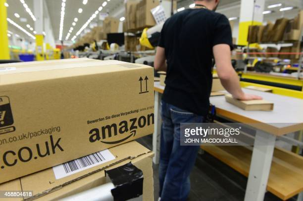 An employee places packed goods on a conveyor belt for shipment at US online retail giant Amazon's Brieselang logistics center west of Berlin on...