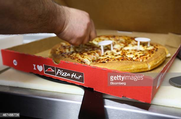 An employee places plastic box supports around a freshly cooked pizza as he prepares a takeaway order for a customer in the kitchen of a Pizza Hut...