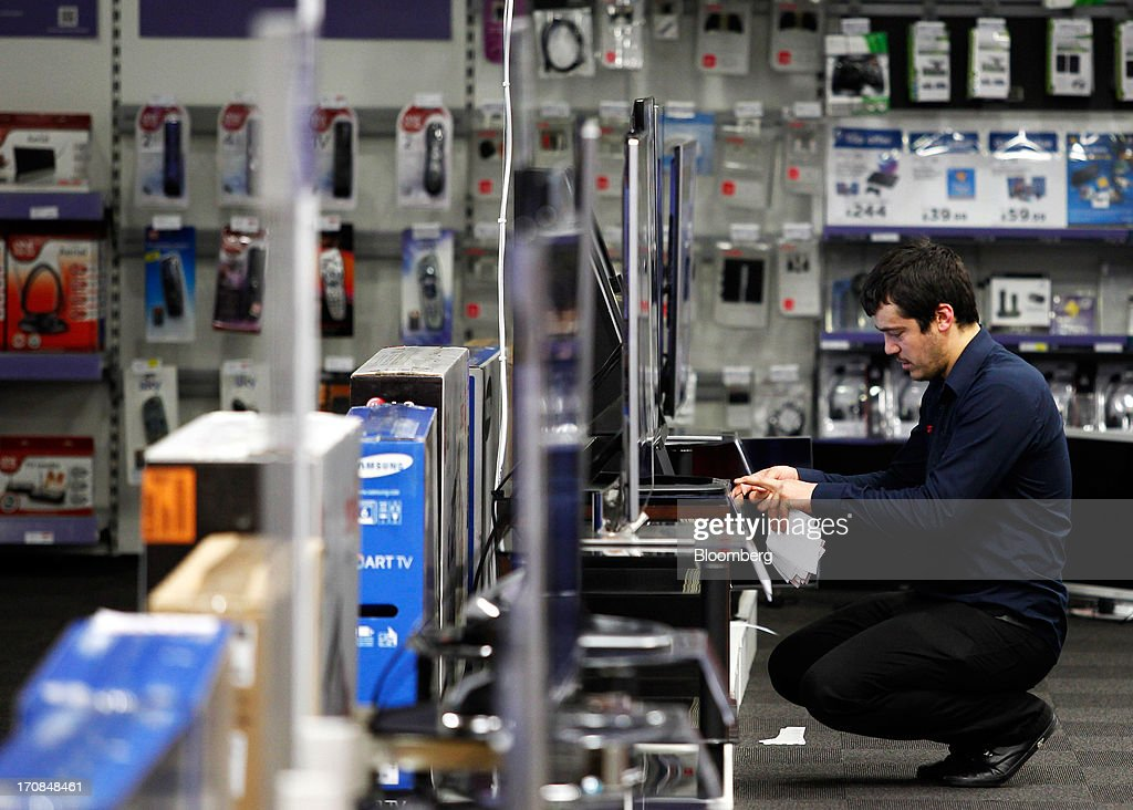 An employee places price information in front of flat screen television display inside a Currys and PC World 2 in 1 store, operated by Dixons Retail Plc, in Manchester, U.K., on Tuesday, June 18, 2013. Dixons Retail Plc, the U.K.'s largest consumer-electronics retailer, said last month it will report annual pretax profit at the 'top end' of analysts' predictions after fourth-quarter revenue beat estimates on increased sales of tablets and services such as software tutorials. Photographer: Paul Thomas/Bloomberg via Getty Images