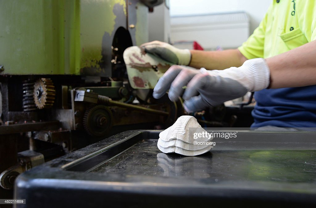 An employee places stitched leather casings for white cricket balls on a tray at the Kookaburra Sports Pty Ltd. plant in Melbourne, Australia, on Tuesday, Nov. 26, 2013. Australian businesses need to boost efficiency to maintain growth in living standards, Reserve Bank of Australia Deputy Governor Philip Lowe said. Photographer: Carla Gottgens/Bloomberg via Getty Images