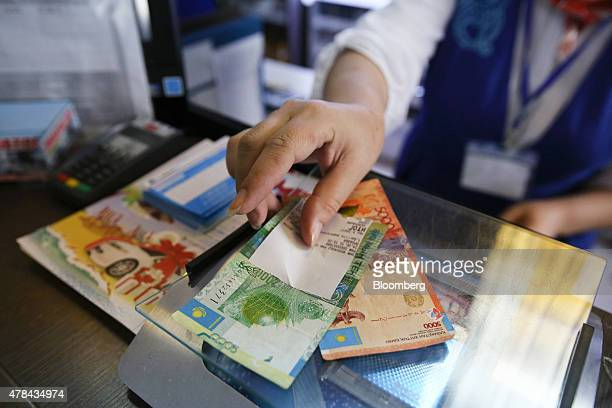 An employee places tenge currency banknotes on the payment counter of a gas station operated by KazMunayGas National Co in Almaty Kazakhstan on...