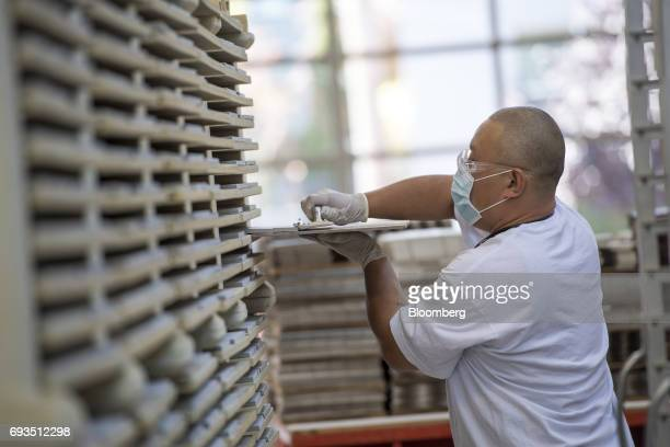 An employee places tile squares to be glazed on a rack at the Heath Ceramics Ltd production facility in San Francisco California US on Friday June 2...