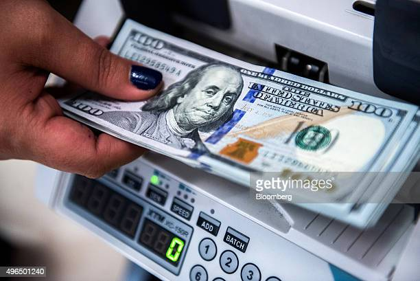 An employee places US onehundred dollar currency banknotes into a money counting machine at a bank branch inside the FHB Commercial Bank Ltd also...