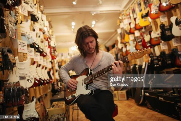 An employee plays a guitar in the Regent Sounds Studios store on Denmark Street on April 20 2011 in London England Denmark Street in the Soho area of...