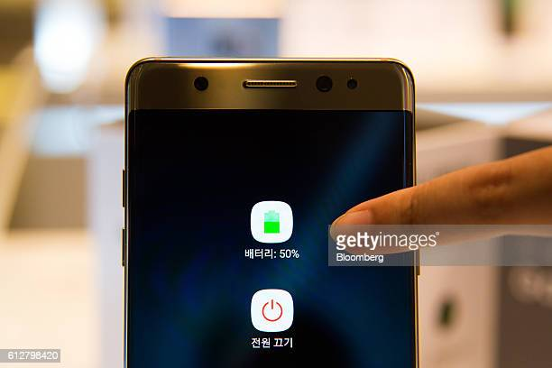 An employee points to a symbol indicating battery capacity displayed on the screen of a Samsung Electronics Co Galaxy Note 7 smartphone at one of the...