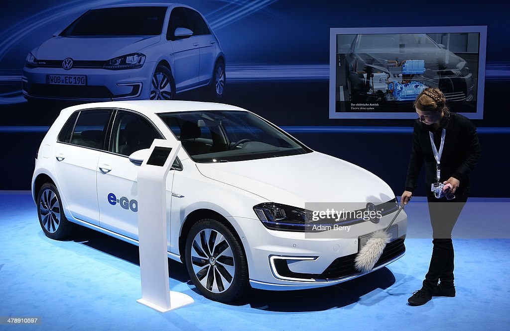An employee polishes a Volkswagen e-Golf automobile at the Electric Mobility Week (e-Mobilitaetswochen), a public Volkswagen (VW) event at the former Tempelhof airport, on March 15, 2014 in Berlin, Germany. The event was designed to promote the company's e-Golf und e-up! automobiles, as well as its other alternative energy powered vehicles.