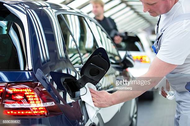 An employee polishes a Volkswagen eGolf electric automobile inside the Volkswagen AG factory in Wolfsburg Germany on Friday May 20 2016 Volkswagen AG...