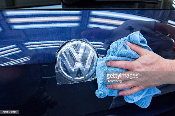 An employee polishes the bodywork of a Volkswagen eGolf electric automobile inside the Volkswagen AG factory in Wolfsburg Germany on Friday May 20...