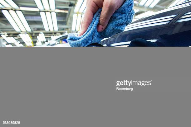 An employee polishes the VW charging port badge on a Volkswagen GTE Golf hybrid automobile inside the Volkswagen AG factory in Wolfsburg Germany on...
