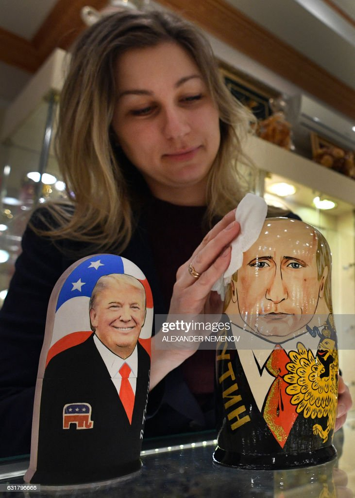 An employee polishes traditional Russian wooden nesting dolls, Matryoshka dolls, depicting US President-elect Donald Trump (L) and Russian President Vladimir Putin at a gift shop in central Moscow on January 16, 2017, four days ahead of Trump's inauguration. / AFP / Alexander NEMENOV