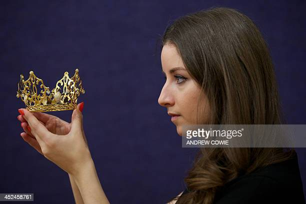 An employee poses as she dispalys a tiara entitled East of Paris designed by Irish born jewellery artist Slim Barrett and worn by Victoria Beckham on...