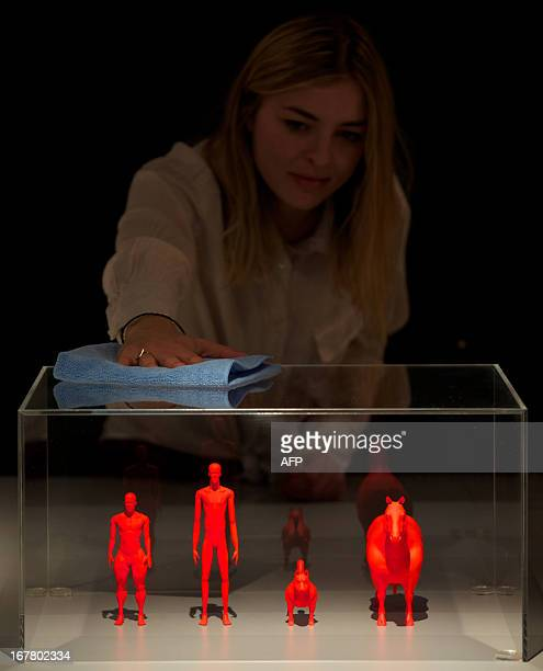 An employee poses behind a case displaying models of the Cyclist Balloonist Pitsky and Hox genetically modified and adapted inhabitants of an...