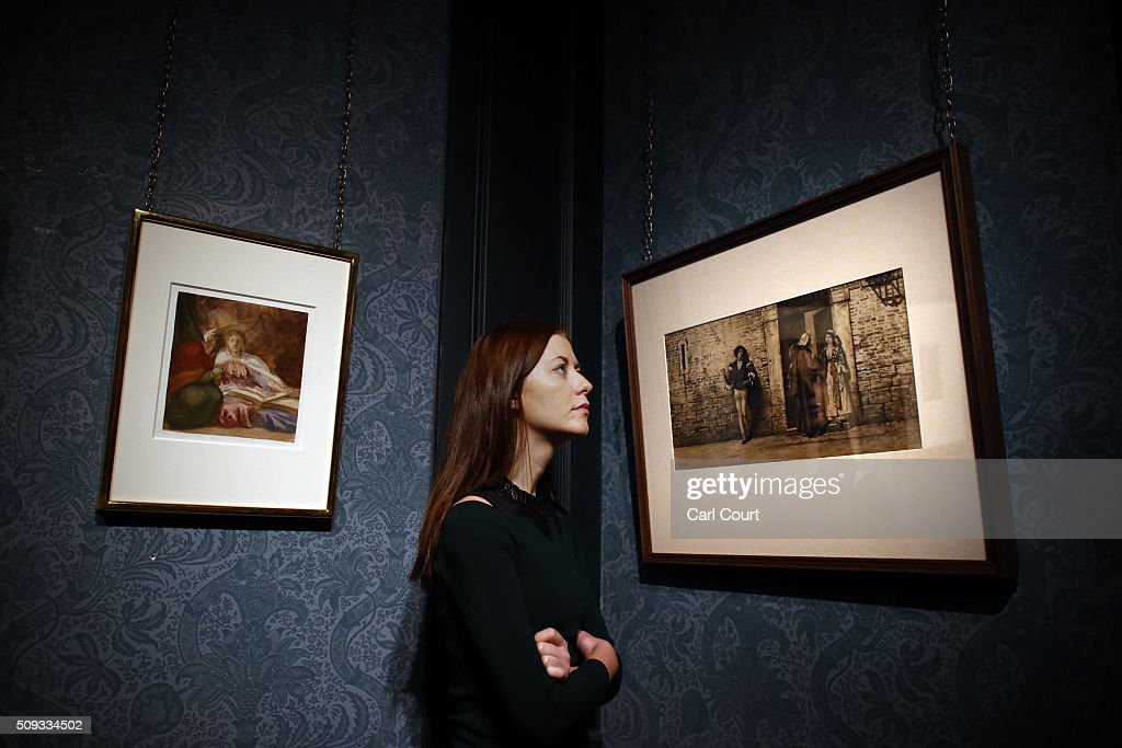 An employee poses between paintings by George Frederick Watts entitled 'Sketch for Britomart and Her Nurse' (L) and Scene from Shakespeare's 'The Merchant of Venice' by Henry Wallis during a preview at Leighton House Museum on February 10, 2016 in London, England. The worst form part of the Pre-Raphaelites on Paper exhibition, which will run from 12th February to 29th May 2016.