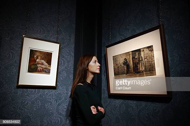 An employee poses between paintings by George Frederick Watts entitled 'Sketch for Britomart and Her Nurse' and Scene from Shakespeare's 'The...