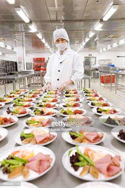 An employee poses for a photograph behind air catering entrees in Guangzhou Nanland Air Catering Co Ltd center on April 7 2009 in Guangzhou China