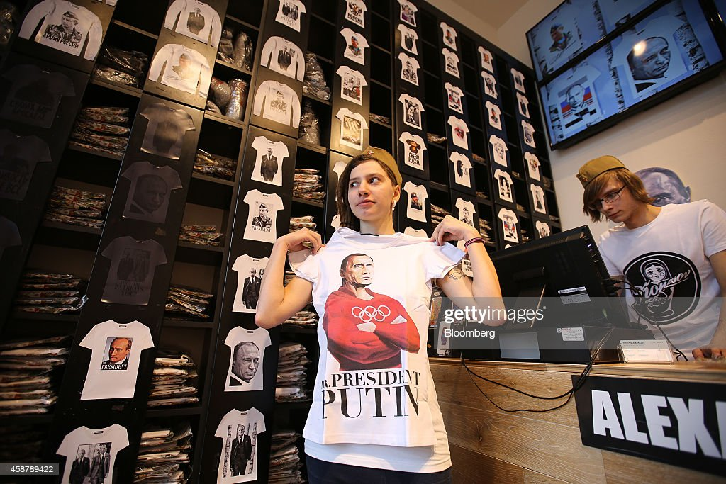 An employee poses for a photograph with a Putin tshirt design from the Patriot collection inside an Alexander Konasov clothing store in Moscow Russia...