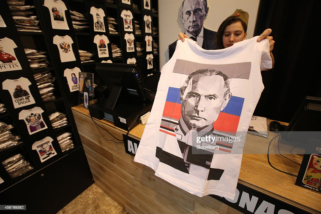 An employee poses for a photograph with a Vladimir Putin tshirt design featuring a Russian national flag from the Patriot collection inside an...