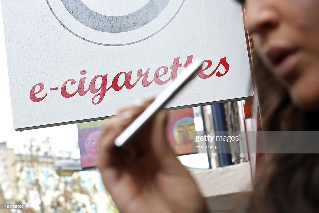 An employee poses for a photograph with a V-Revolution e-cigarette outside the company's store in London, U.K., on Wednesday, Oct. 16, 2013. The U.S. Food and Drug Administration is set to decide this month whether to lump e-cigarettes in with conventional smokes as part of its oversight of the $90 billion U.S. tobacco market. Photographer: Chris Ratcliffe/Bloomberg via Getty Images