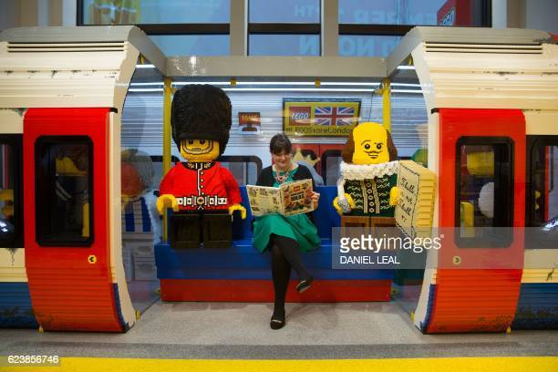 An employee poses for a picture sitting inside a London Underground tube train carriage made with LEGO pieces before the official opening of the new...