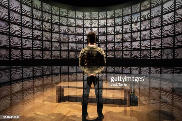 An employee poses in front of 'Fratelli d'Italia' by Matthias Schaller at the Victoria and Albert Museum during a photocall for their Opera Passion...