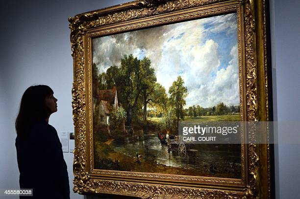 An employee poses next a painting by British artist John Constable entitled 'The Hay Wain' during a photocall at the Victoria and Albert Museum in...