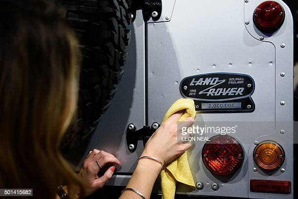 An employee poses next to a commemorative badge on the twomillionth Land Rover Defender offroad vehicle during a photocall promote the forthcoming...