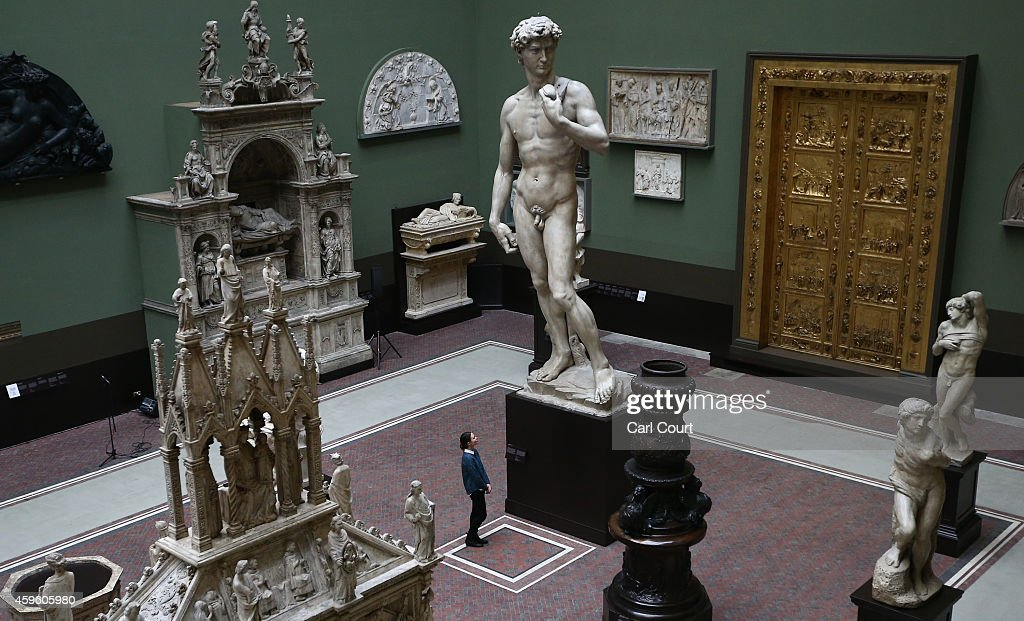 An employee poses next to a five metre high cast of Michelangelo's David during a press preview for the newly renovated Weston Cast Court at the...