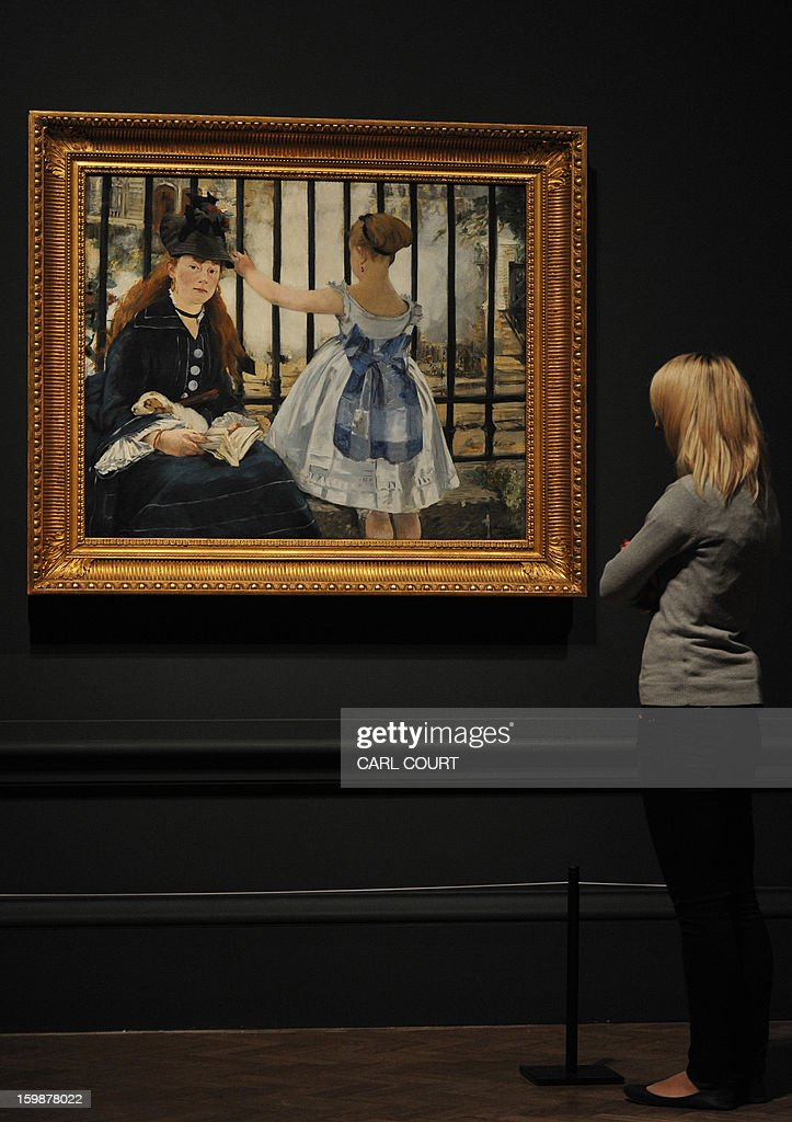 An employee poses next to a painting by French artist Edouard Manet entitled 'The Railway' at the Royal Academy of Arts in central London on January 22, 2013. Forming part of the 'Manet: Portraying Life' exhibition, it is due to be displayed from January 26 to April 14.