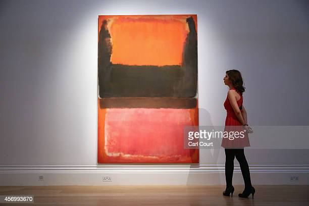An employee poses next to a painting by Mark Rothko entitled 'Red Brown Black and Orange' Due to be auctioned in New York on November 7th it is...