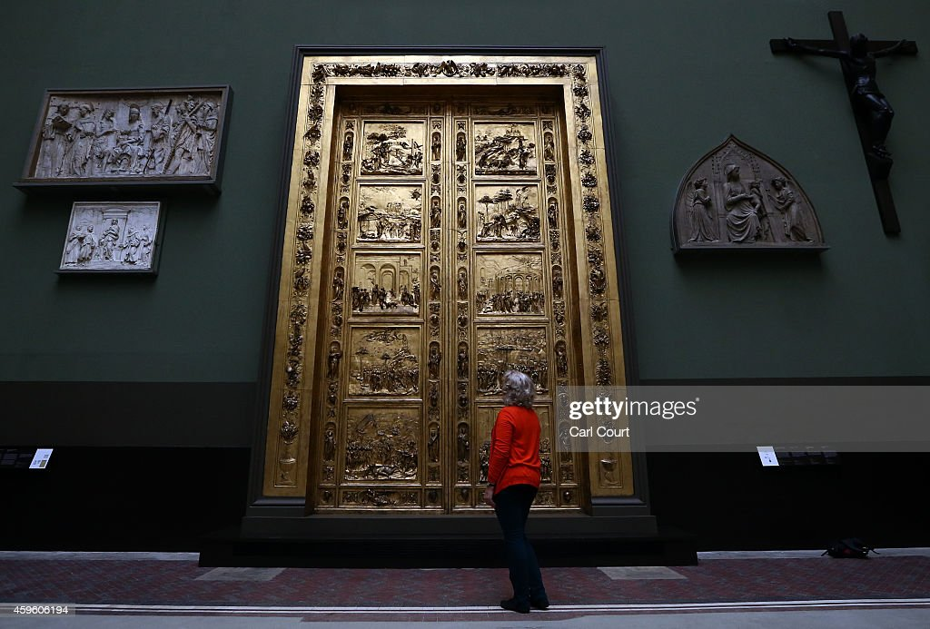 An employee poses next to a set of electrotype doors cast from the Gates of Paradise at Florence Cathedral measuring over seven and a half meters in...