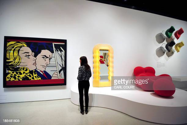 An employee poses next to 'In the Car' artwork by Roy Lichtenstein dispalyed at the Pop Art Design exhbition at the Barbican in central London on...