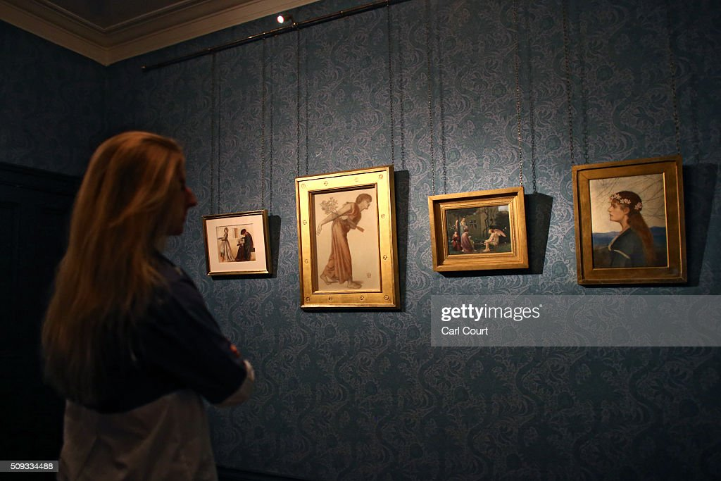 An employee poses next to paintings during a preview at Leighton House Museum on February 10, 2016 in London, England. The work forms part of the Pre-Raphaelites on Paper exhibition, which will run from 12th February to 29th May 2016.