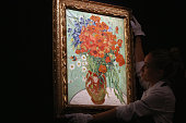 An employee poses with a painting by Vincent Van Gogh entitled 'Vase with Dasies and Poppies' during a press preview at Sotheby's on October 10 2014...