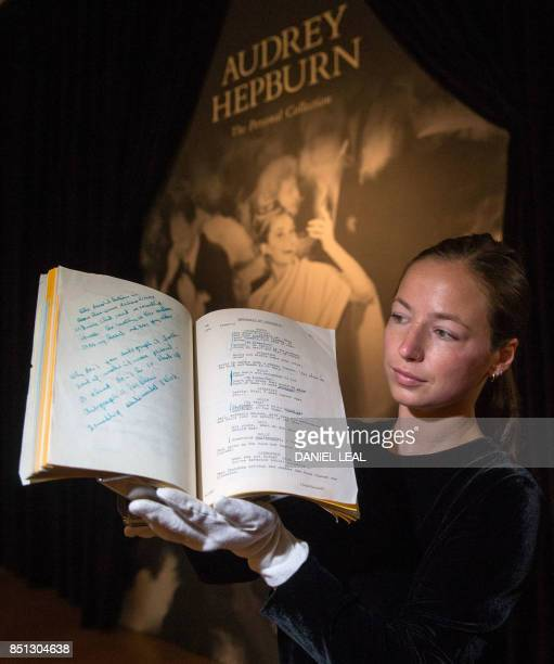 An employee poses with a working script for the 1961 production 'Breakfast at Tiffanys' with a reserve price of £60000 £90000 during a preview of...