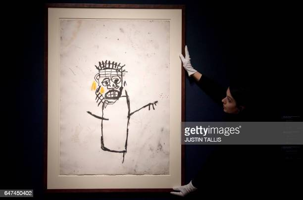 An employee poses with an artwork by American artist JeanMichel Basquiat entitled 'Untitled' with an estimated value of 115 million GBP during a...
