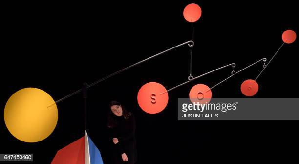 An employee poses with an artwork by American sculptor Alexander Calder entitled 'Untitled' with an estimated price of 3555 million GBP during a...