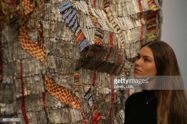 An employee poses with an artwork by 'untitled ' by Benin artist Leonce Raphael Agbodjelou priced at 40006000 pounds / 50007500 dollars during a...