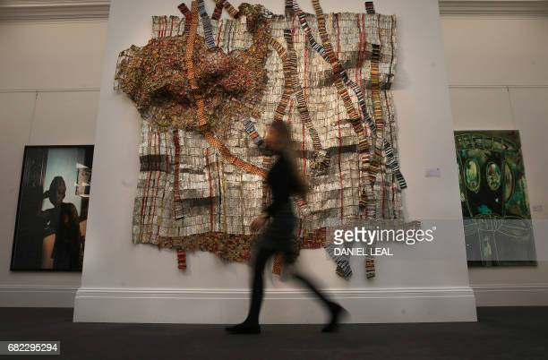 An employee poses with an artwork 'untitled ' 2012 by Benin artist Leonce Raphael Agbodjelou priced at 4000 6000 pounds / 5000 7500 dollars during a...
