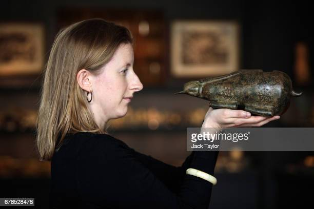 An employee poses with an early Islamic bronze portable cannon from Syria circa 1300 at 5 Cromwell Place on May 4 2017 in London England British art...