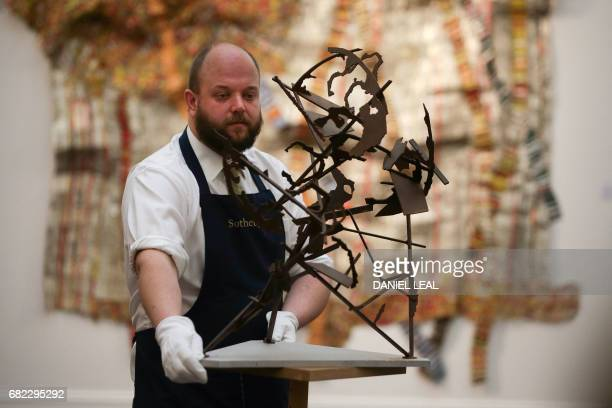An employee poses with with an artwork entitled 'World On Its Hinds Legs' 2010' by South African artist William Kentridge with an starting price of...