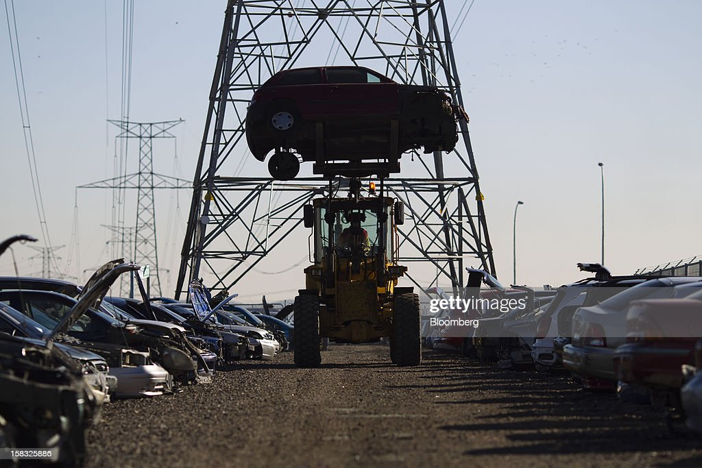 An employee positions a scrapped vehicle chassis using a front-loader in the yard of the Desguaces La Torre scrapyard in Madrid, Spain, on Thursday, Dec. 13, 2012. Spain has completed the debt sales it planned for this year and started raising funds for 2013, buying time for Prime Minister Mariano Rajoy as he decides whether to seek a European bailout. Photographer: Angel Navarrete/Bloomberg via Getty Images