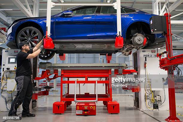 An employee positions a Tesla Model S automobile during battery pack fitting on the final assembly at the Tesla Motors Inc factory in Tilburg...